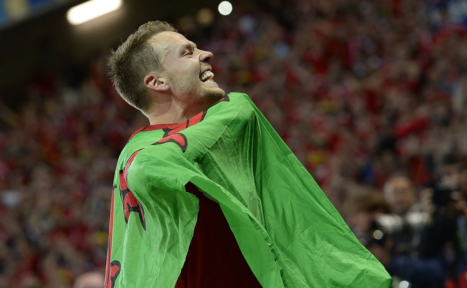 Wales' defender Chris Gunter, who missed his brother's wedding for the quarter-final match, celebrates his team's win with the country's flag. AFP