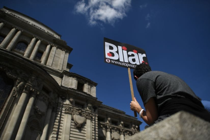 A demonstrator holds a placard during a protest near the venue of the publication of the Iraq Inquiry report in London. AFP