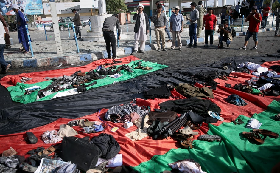 Afghans look at property left behind by victims of an explosion that struck a protest march, that is displayed on a large representation of the Afghan flag, in Kabul, Afghanistan, Saturday, 23 July, 2016. AP