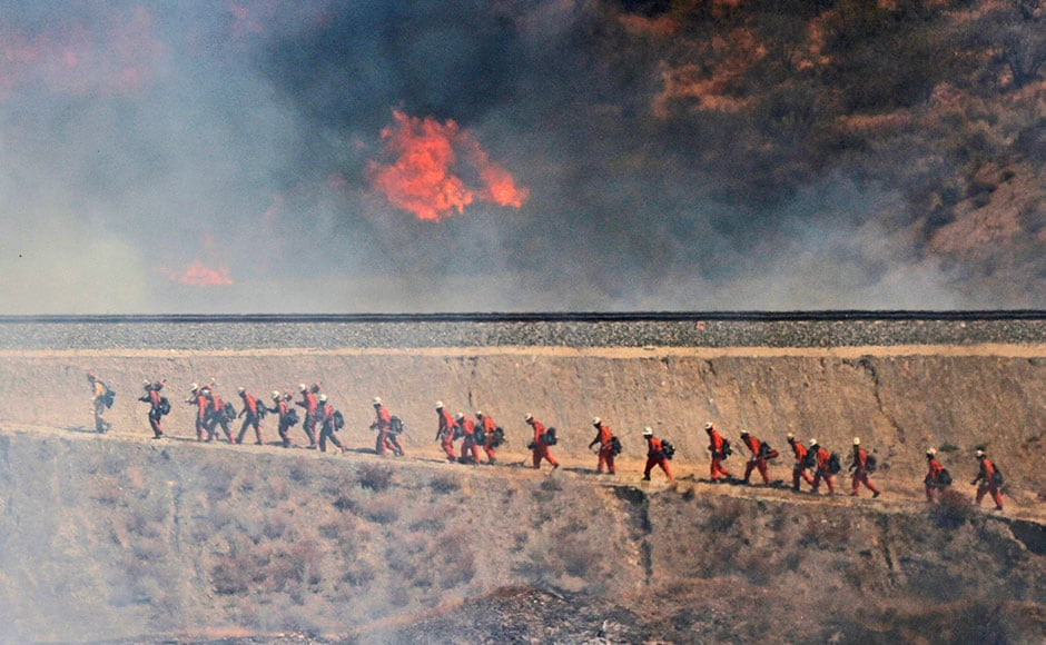A fire crew approaches as a wildfire burns  in Santa Clarita, Calif. The fire erupted shortly after 2 p.m. Friday next to State Route 14 in Santa Clarita. No homes are immediately threatened, but fire officials say evacuations have been ordered from Soledad Canyon to Agua Dulce Canyon Road. AP