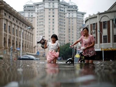 Flood waters burst river banks and submerged at least 12 villages. AP