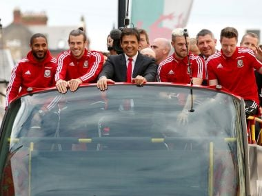Wales soccer players ride an open top bus along with Chris Coleman. AP