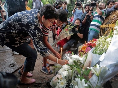 People offer flowers and light candles as tribute to those killed in the Dhaka attack. AP.