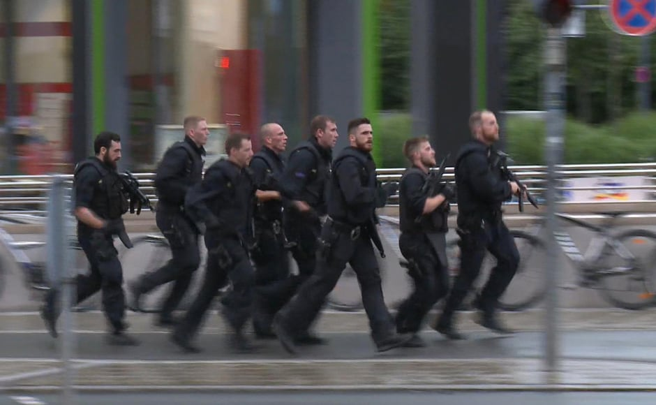 In this grab taken from a video, police run in the area of the Olympia Einkaufszentrum mall, after a shooting was reported in Munich. AP
