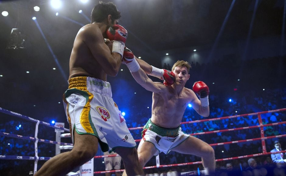 Vijender Singh fights with Australia's Kerry Hope during their fight for the WBO Asia Pacific Super Middleweight title in New Delhi. AP