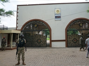 Soldiers stand guard outside the bullet-scarred main gate of the presidential palace in Juba, where clashes between rival units this week left scores dead and set off battles elsewhere in the city. AFP