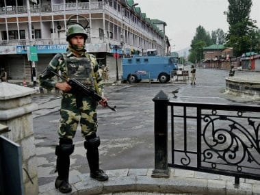Police personnel guards the area under curfew. PTI