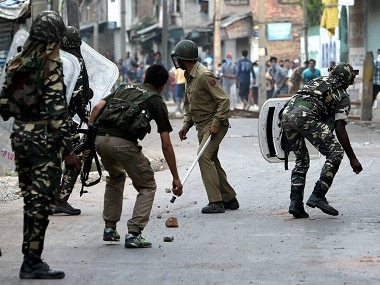 Security personnel chasing away stone throwing youths during a clash in Srinagar on Thursday. PTI