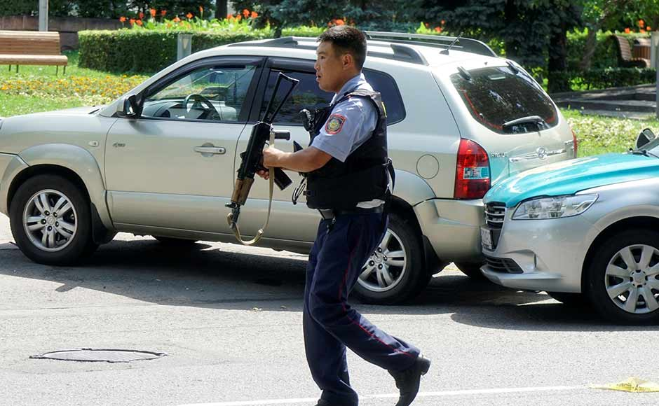 A policeman runs across the street in Almaty. While fleeing from the police station, one of the gunmen shot and killed a local resident before hijacking his car, the police said. Reuters