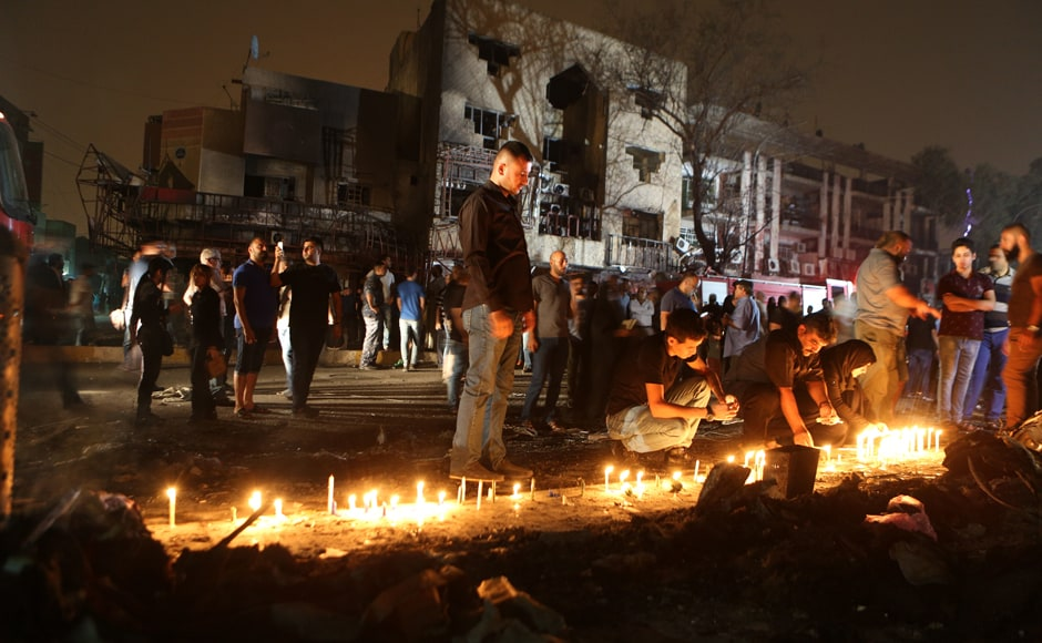 People light candles at the scene of the attack on Sunday night. Karrada was busy at the time as Iraqis eat out and shop late during the Muslim fasting month of Ramzan, which ends next week with the Eid al-Fitr festival. Photo Courtesy: AP
