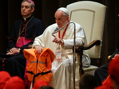 Pope Francis holds a life jacket vest of Syrian girl who died while trying to reach the Greek island of Lesbos, during a meeting with some 400 children coming by train from the region of Calabria, at the Vatican. The pontiff's advocacy for refugee rights faces a diplomatic test Wednesday when he begins a five-day visit to Poland, where a populist government has slammed the door on most asylum seekers. File photo AP