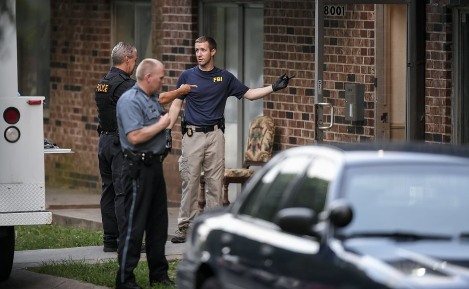 FBI evidence recovery team members search inside the Waldo Heights apartment complex in Kansas City on Sunday in connection to the shooting incident. AP