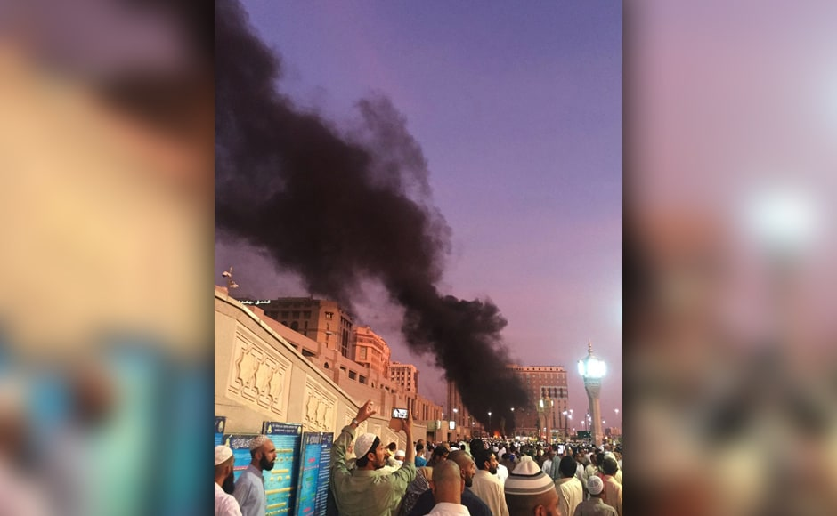 People stand near the explosion site as two suicide bombers struck in different cities in Saudi Arabia. Photo Courtesy: AP