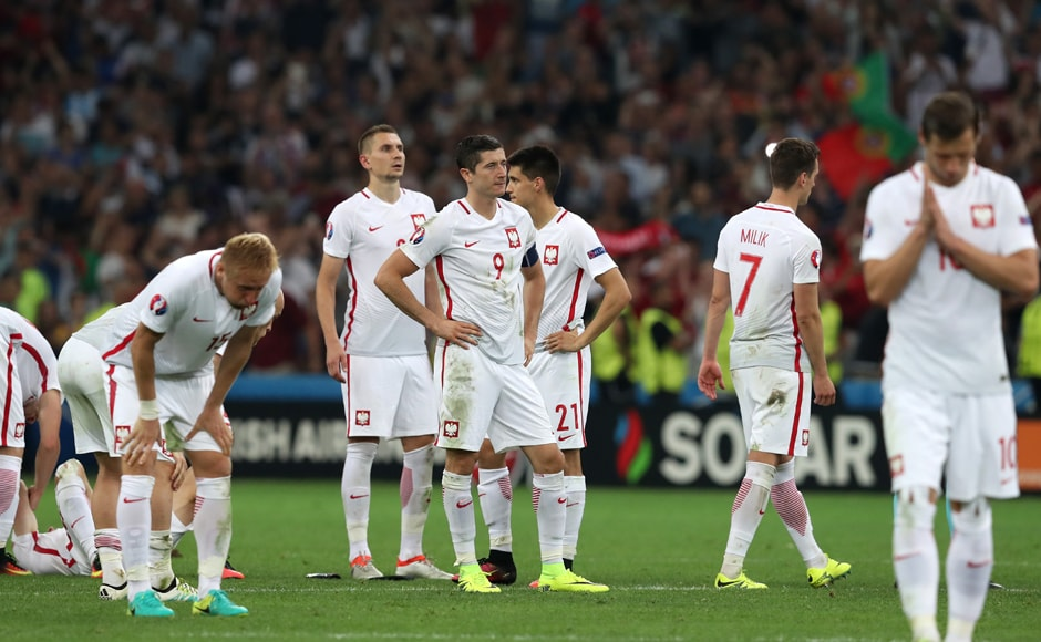 Poland's Robert Lewandowski and his teammates look dejected after their loss to Portugal. AP