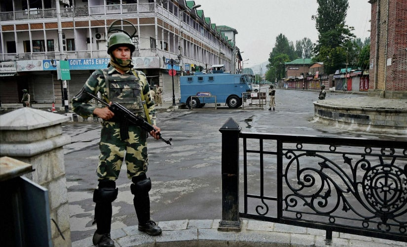 Security personnel guard the roads during the curfew. PTI