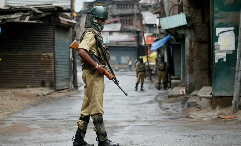 Police guards a deserted street during the curfew in the state. PTI