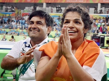 RPT...Rio de Janeiro: India's Sakshi Malik with her coach Kuldeep Singh, celebrate after winning bronze against Kyrgyzstan's Aisuluu Tynybekova in the women's wrestling freestyle 58-kg competition, at the 2016 Summer Olympics in Rio de Janeiro, Brazil on Wednesday. PTI Photo by Atul Yadav  (PTI8_18_2016_000075B)