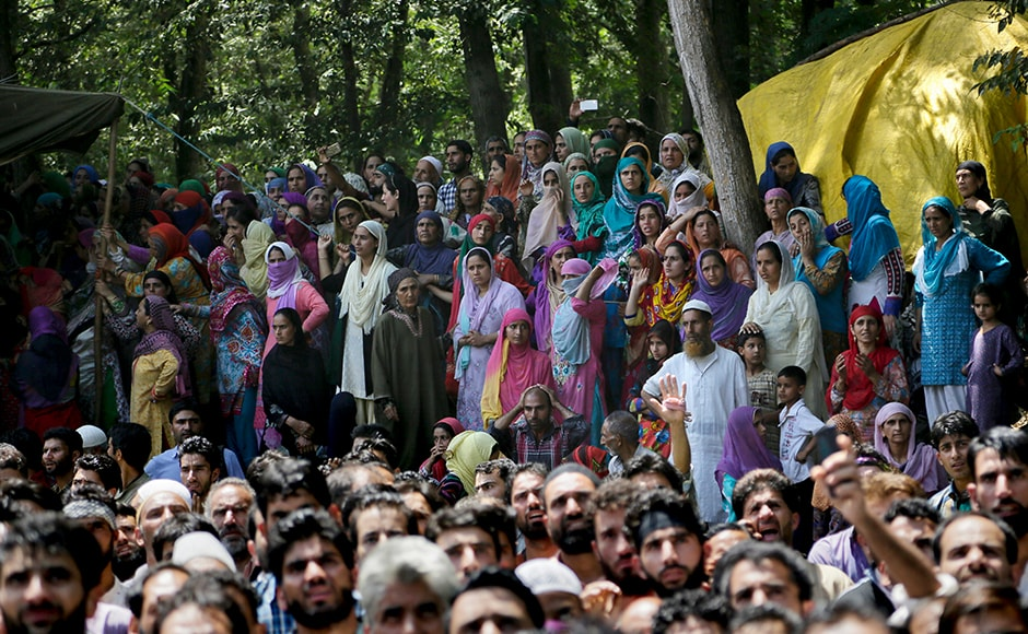 Kashmiri villagers watch a joint funeral of the four civilians at Aripanthan village. Separatists have already extended their protest shutdown to 18 August. All educational institutions, shops, public transport and other businesses have remained shut since 9 July, a day after Hizbul Mujahideen commander Burhan Wani was killed. AP