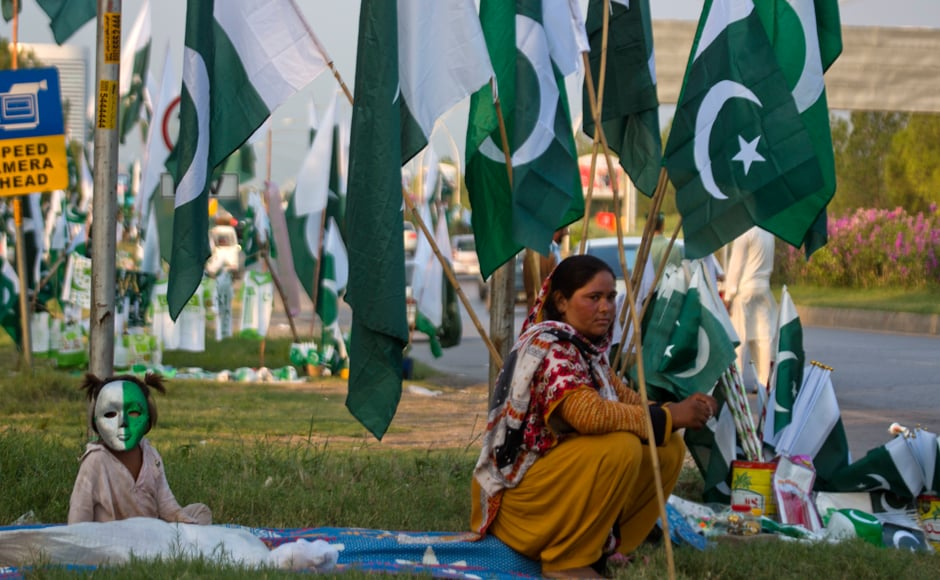 A Pakistani vendor waits for customers with her daughter to sell national flags, badges and masks ahead of Pakistan Independence Day in Islamabad, Pakistan, Friday, Aug. 12, 2106. Pakistani nation will celebrate its 70th Independence Day on Aug. 14, 2016. AP