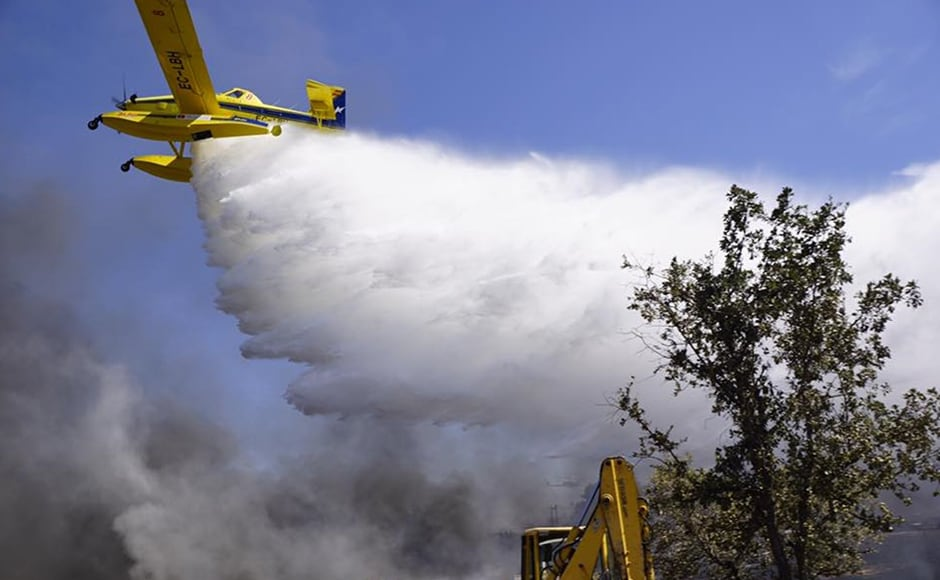 A fire fighting plane flies over the parking lot of the open air music festival. AP