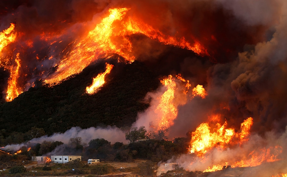 A Southern California wildfire raged virtually unchecked in thick brush on Wednesday after destroying dozens of houses near a highway corridor between Los Angeles and Las Vegas and forcing as many as 80,000 residents to flee their homes. Reuters