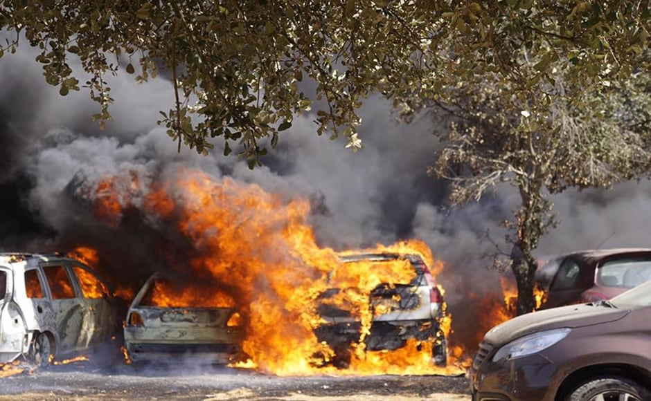 Cars burn in a parking lot in Barragem da Povoa in eastern Portugal on Wednesday. Authorities said there were no casualties in the blaze which forced the evacuation of some 4,000 people at the festival. AP