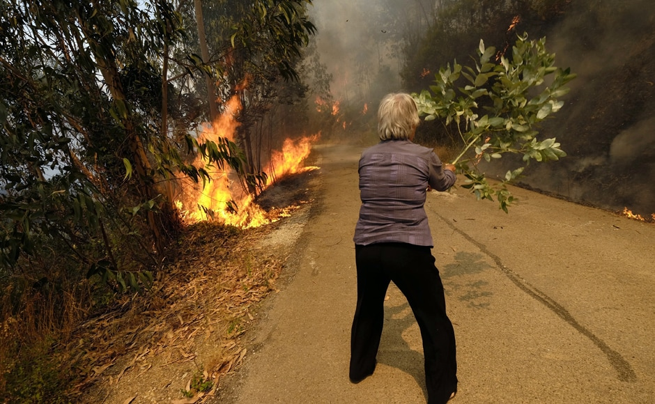 A woman uses a tree branch to fight a fire on the road leading to the village of Parada, near Mortagua. The Madeira fire forced the evacuation of more than 1,000 residents and tourists in the islands. Residents described chaotic nighttime scenes, with people fleeing the flames by car at high speed on the wrong side of the road. AP