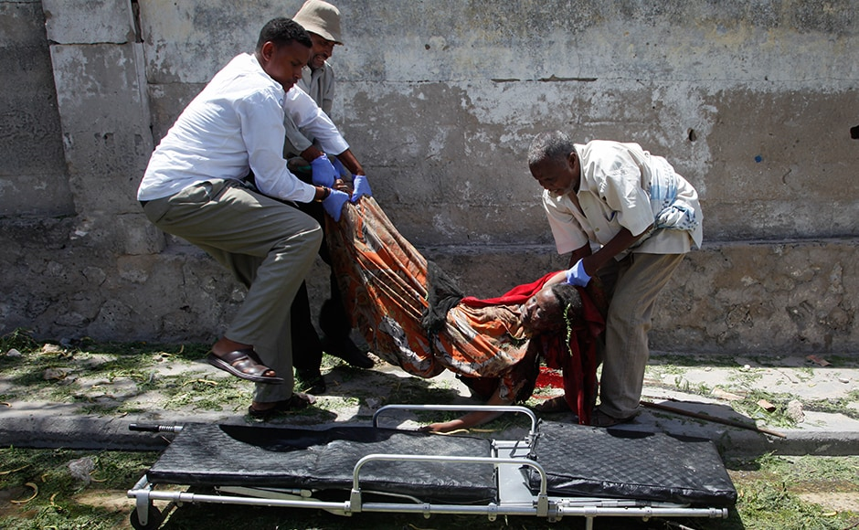 The blast damaged nearby hotels often frequented by government officials and business executives. A woman who was among the 12 dead is being carried away after the blast by some Somali men. AP