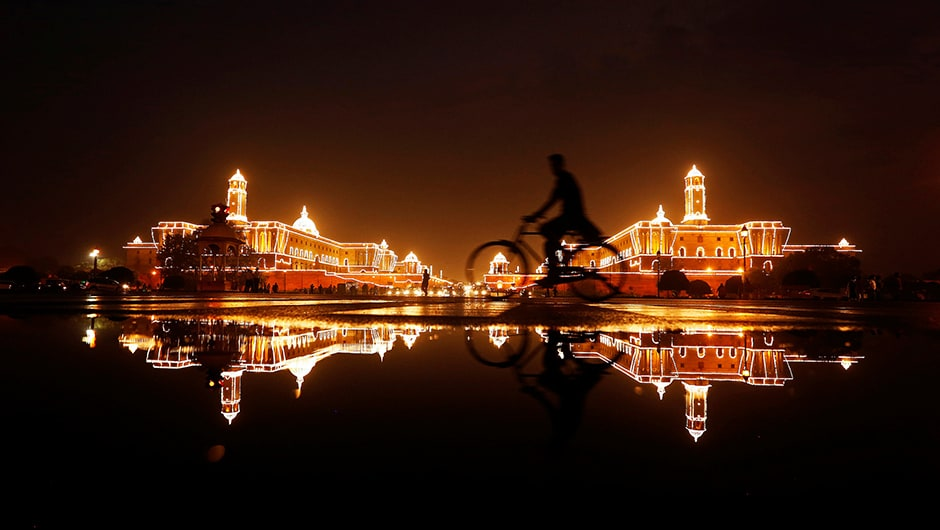 A cyclist rides past the illuminated Raisina Hills ahead of India's Independence Day celebrations in New Delhi, India. Reuters
