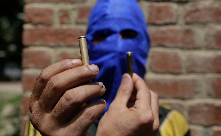 A masked Kashmiri youth shows empty bullet cartridges allegedly fired by government forces at the four civilians at Aripanthan village in Srinagar. More than 7,000 civilians have also been injured in action by government forces hundreds of them have lost eyesight and others maimed for life due to firearm injuries. AP