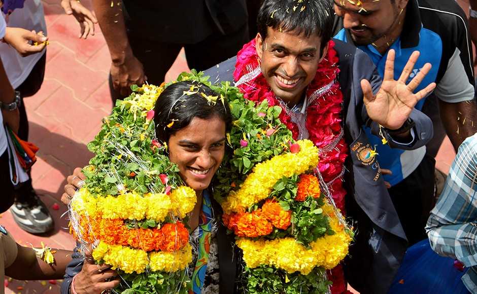 P.V. Sindhu, left, who won one of India's two medals at the Rio de Janeiro Olympics and her coach Pullela Gopichand wave to the cameras during their reception at the Gopichand Academy in Hyderabad. The 21-year-old who won the silver medal in women's singles badminton event is also the first Indian woman to win an Olympic silver medal. AP