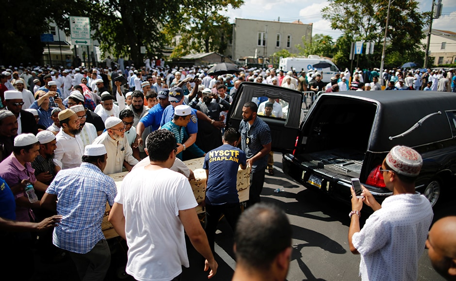 Community representatives move the coffin to the hearse as they gather for the funeral service of the Imam. The police charged Morel, 35, with two counts of second-degree murder.