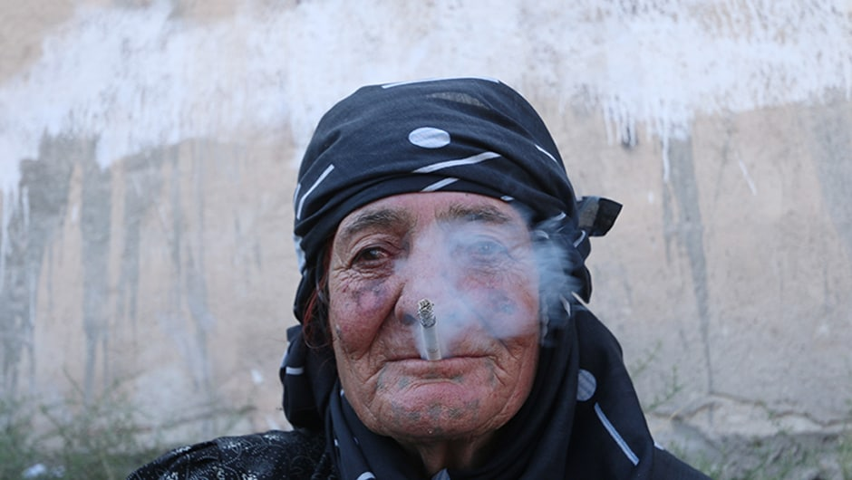 A woman smokes as she rests after she was evacuated by the SDF fighters .  <em>AFP</em> footage showed the city's streets strewn with rubble and a wall still painted with the jihadists' black and white flag. Reuters