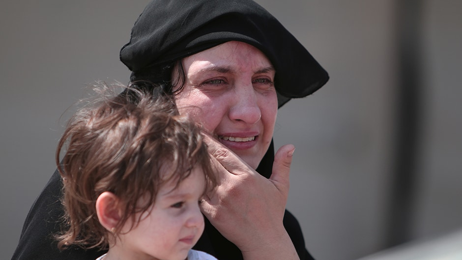 "A woman sits with her child after they were evacuated by the SDF fighters from Manbij.  ""Among the civilians taken by Islamic State there were people used as human shields but also many who chose voluntarily to leave the town due to fear of reprisals"" by the SDF, observatory head Rami Abdel Rahman said. Reuters"