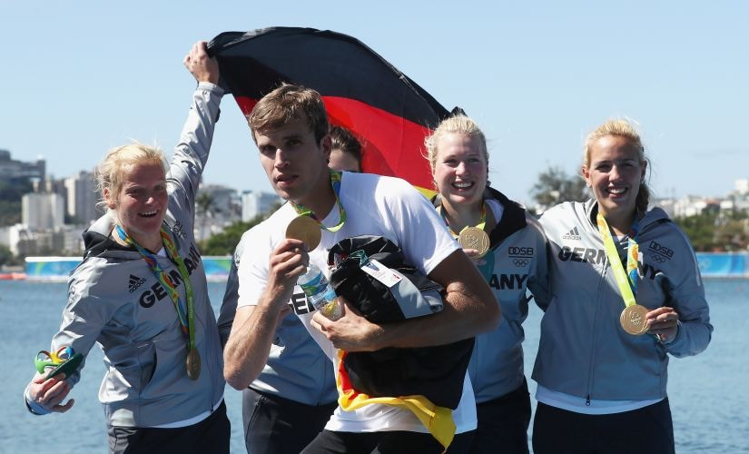 Gold medalist Philipp Wende of Germany jokes around following the medal ceremony for the Women's Quadruple Sculls Final. Getty