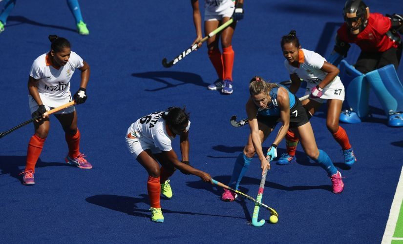 Maria Cavallero of Argentina is tackled by Rani during the Women's pool B hockey match. Getty