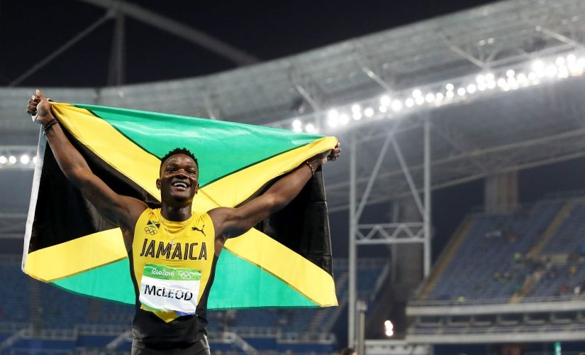 Omar Mcleod celebrates with the flag of Jamaica after winning the gold medal in the Men's 110m Hurdles. Getty