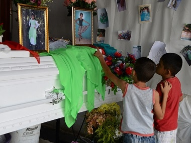 Two boys attend the wake of late Honduran girl Jennifer, 10, in San Carlos. AFP