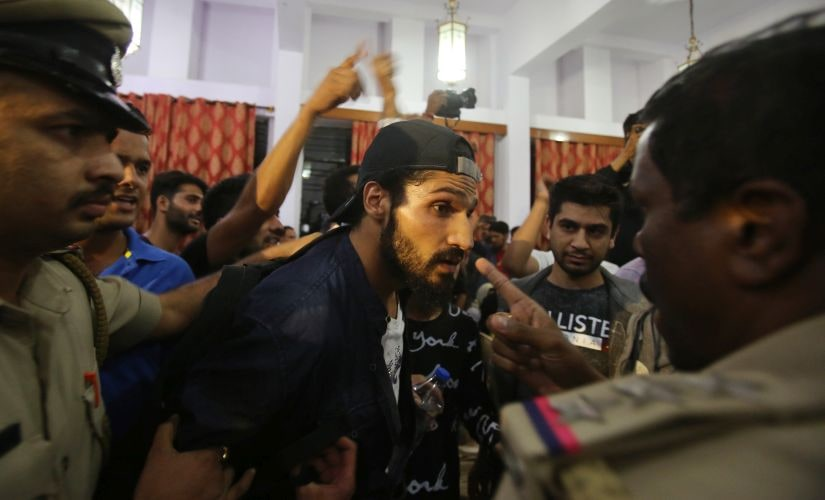 Kashmiri rapper Roshan Ellahi, also known as MC Kash, centre, is confronted by Indian police at an event organised by Amnesty International in Bangalore. AP