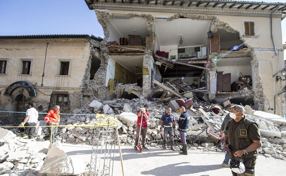 Rescuers stand by a collapsed house following an earthquake in Amatrice, central Italy on Wednesday, 24 August, 2016. A strong earthquake in central Italy reduced three towns to rubble as people slept early Wednesday. AP