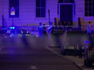 Police officers stand behind cordon tape after a knife attack in London Thursday, Aug. 4, 2016. London police say a woman has died and some others were injured in a knife attack in a central part of the city. (Sky News via AP)