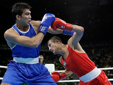 Fazliddin Gaibnazarov, right, fights India's Manoj Kumar during men's lightwelter weight 64-kg preliminary boxing match. AP