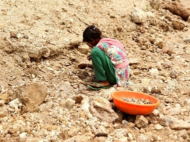 Gudiya, 13, breaks away pieces of mica from rocks in an illegal open cast mine in Koderma, Jharkhand. Reuters