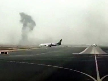 """This image made from video shows smoke rising after an Emirates flight crash landed at Dubai International Airport on Wednesday, Aug. 3, 2016. The plane at right was unaffected Dubai-based airline Emirates has confirmed that there were no fatalities on a flight from India that crash-landed . The carrier says """"all passengers and crew are accounted for and safe."""" It raised the number of people onboard the flight to 300, saying there were 282 passengers, 18 crew.(Hayen Ayari via AP)"""