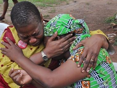 """""""Bring Back Our Girls"""" co-founder Obiageli Ezekwesili, left, console Esther Yakubu, mother of one of the kidnapped school girls, after she saw her daughter in a video release by Boko haram during a briefing in Abuja, Nigeria. Sunday Aug. 14, 2016 . The mother of one of the Chibok girls kidnapped more than two years ago by Nigeria's Islamic extremists on Sunday saw the first proof her daughter is alive — a video of her begging Nigeria's government to exchange detained militants for the girls' freedom. (AP Photo/Olamikan Gbemiga)"""