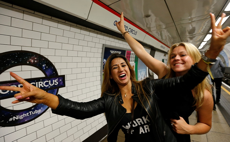 Passengers pose for a photograph as they wait for the Night Tube train service at Oxford Circus on the London underground system. Reuters