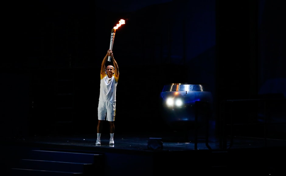 Former Brazilian marathon runner Vanderlei Cordeiro de Lima holds the Olympic torch before lighting the cauldron at the opening ceremony. Reuters