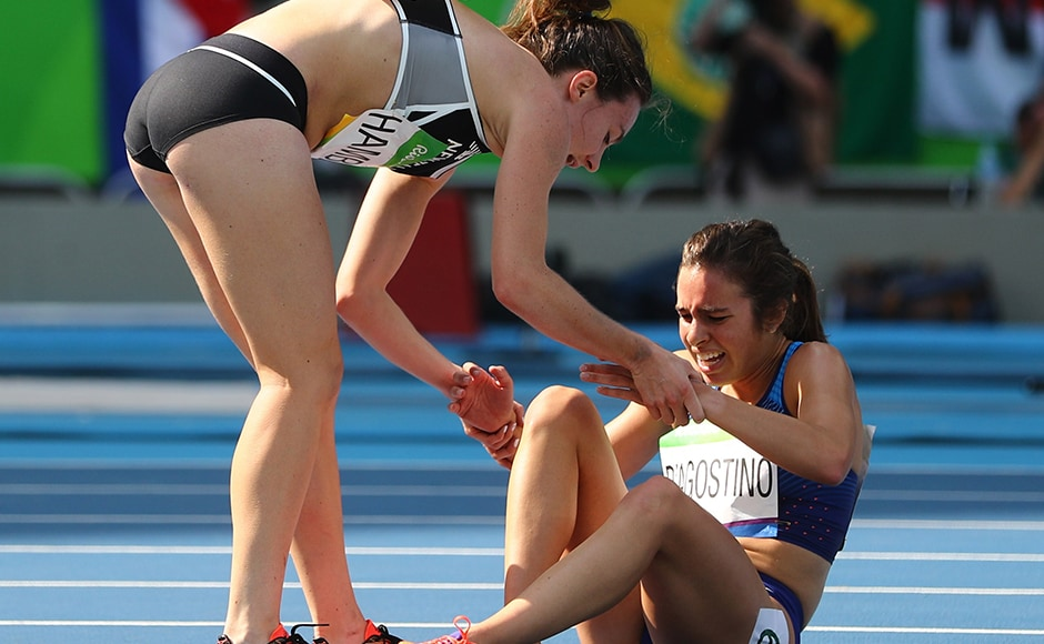 Nikki Hamblin of New Zealand stops running during the race to help fellow competitor Abbey D'Agostino of USA after D'Agostino suffered a cramp in Women's 5000m Round 1. Reuters