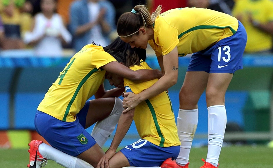 Rafaelle and Erika console teammate Marta of Brazil after losing their game against Sweden in the penalty shoot-out. Reuters