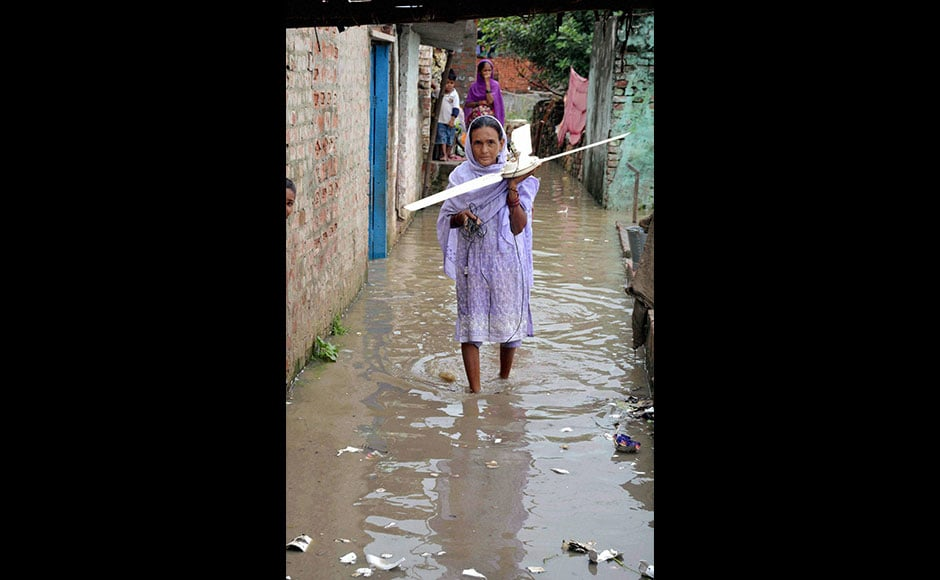 Although the Disaster Management Department said that no district was in the grip of floods, water entered a few villages located close to the low-lying areas. It disrupted normal life as people were forced to traverse through floodwater. Photo: PTI